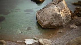 Härlig lugna stenig havslinje och liten stenig strand mellan klippor tomt uppblåsbart fartyg på stranden lager videofilmer