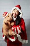 Härlig lycklig asiatisk flicka i Santa Claus kläder Arkivfoton