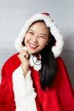 Härlig lycklig asiatisk flicka i Santa Claus kläder Arkivbild