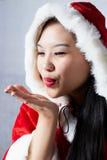 Härlig lycklig asiatisk flicka i Santa Claus kläder Arkivfoto