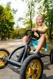 Härlig lycklig bil för liten flickaridningleksak in Arkivfoto