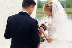 Härlig lycklig blond brud som tar löften med stiliga brudgumclo Royaltyfri Foto