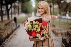 Härlig lycklig blond kvinna i plädlaget som rymmer en ljus bouq arkivbilder