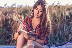 Härlig lycklig brunettflicka i ett fält, skjorta Nya idéer för begrepp som skriver i anteckningsbok Vila på luft Studenten Royaltyfri Foto