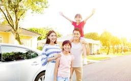Härlig lycklig familjstående utanför deras hus royaltyfri fotografi
