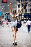 Härlig lycklig flicka med en ryggsäckpåse som går på stadsgatan och har gyckel Kvinnan går handen som bär upp sportsommardräkten arkivfoton