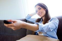 Härlig lycklig hållande ögonen på TV för ung kvinna och innehavfjärrkontroll hemma arkivbilder