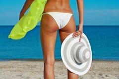 Härlig lycklig kvinna i den vita bikinin med den gula uppblåsbara madrassen på stranden Royaltyfri Fotografi