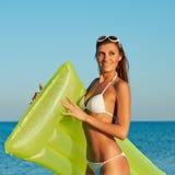 Härlig lycklig kvinna i den vita bikinin med den gula uppblåsbara madrassen på stranden Arkivfoton