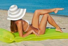 Härlig lycklig kvinna i den vita bikinin med den gula uppblåsbara madrassen på stranden Arkivbild