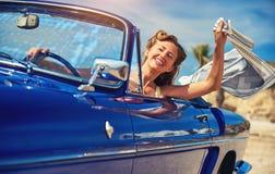 Härlig lycklig kvinna i en bil arkivfoto