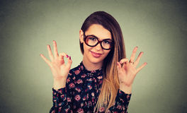 Härlig lycklig kvinna i exponeringsglas som visar det ok tecknet fotografering för bildbyråer
