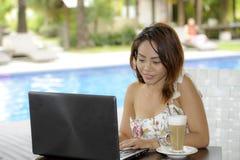 Härlig lycklig kvinna i sommarklänning utomhus på den trevliga coffee shop som har frukostnätverkande eller arbete med bärbar dat Fotografering för Bildbyråer