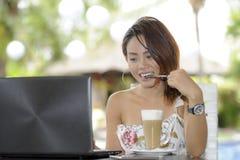 Härlig lycklig kvinna i sommarklänning utomhus på den trevliga coffee shop som har frukostnätverkande eller arbete med bärbar dat Arkivbild