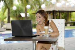 Härlig lycklig kvinna i sommarklänning utomhus på den trevliga coffee shop som har frukostnätverkande eller arbete med bärbar dat Royaltyfri Bild