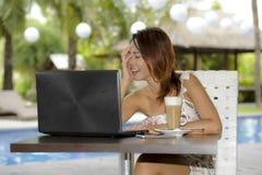 Härlig lycklig kvinna i sommarklänning utomhus på den trevliga coffee shop som har frukostnätverkande eller arbete med bärbar dat Arkivfoton