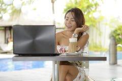 Härlig lycklig kvinna i sommarklänning utomhus på den trevliga coffee shop som har frukostnätverkande eller arbete med bärbar dat Royaltyfri Fotografi