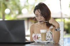 Härlig lycklig kvinna i sommarklänning utomhus på den trevliga coffee shop som har frukostnätverkande eller arbete med bärbar dat Arkivfoto