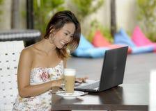 Härlig lycklig kvinna i sommarklänning utomhus på den trevliga coffee shop som har frukostnätverkande eller arbete med bärbar dat Royaltyfria Foton