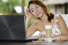 Härlig lycklig kvinna i sommarklänning utomhus på den trevliga coffee shop som har frukostnätverkande eller arbete med bärbar dat Royaltyfria Bilder