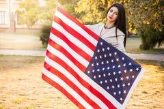 Härlig lycklig kvinna med amerikanska flaggan som firar självständighetsdagen royaltyfria foton