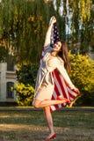 Härlig lycklig kvinna med amerikanska flaggan som firar självständighetsdagen arkivfoton