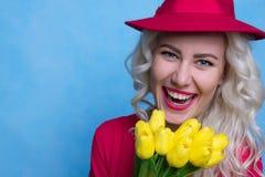 Härlig lycklig kvinna med buketten av blommor mot barn för fjäder för bakgrundsbegreppsblomma vitt gult royaltyfri fotografi