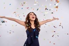 Härlig lycklig kvinna på berömpartiet med att falla för konfettier royaltyfri bild
