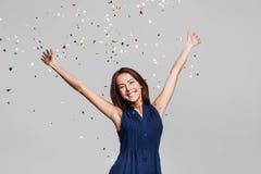 Härlig lycklig kvinna på berömpartiet med konfettier som överallt faller på henne Helgdagsafton för födelsedag som eller för nytt arkivfoton