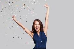 Härlig lycklig kvinna på berömpartiet med konfettier som överallt faller på henne Helgdagsafton för födelsedag som eller för nytt royaltyfria foton