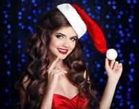 Härlig lycklig le flicka i den santa hatten med röda kanter som poserar f royaltyfri fotografi
