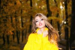 Härlig lycklig le flicka med långt hår som bär det stilfulla omslaget som poserar i höstdag Ursnygg utomhus- stående royaltyfri fotografi