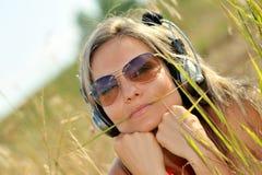 härlig lycklig lyssnande musik till kvinnan royaltyfria bilder