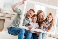 Härlig lycklig rödhårig manfamilj som tillsammans sitter och ser till och med den vita ramen arkivfoton