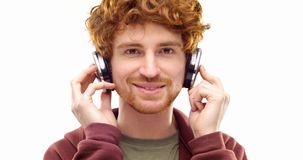 Härlig lycklig rolig ung vuxen rödhårig manman som lyssnar till musik genom att använda hörlurar och att dansa Personhandling Fol lager videofilmer