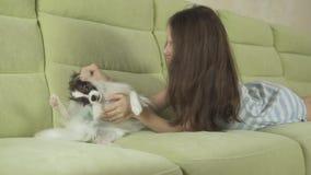 Härlig lycklig tonårs- flicka som har gyckel som spelar med hennes video för längd i fot räknat för hundPapillon kontinentala Toy arkivfilmer