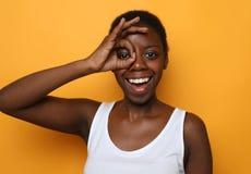 Härlig lycklig ung afrikansk kvinna som isoleras över gul bakgrund arkivbilder