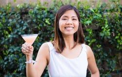 Härlig lycklig ung asiatisk kvinna som tycker om en martini Arkivbild