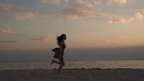 Härlig lycklig ung flickaspring längs stranden och vinka lyckligt henne armar Ung kvinna på solnedgången på stranden arkivfilmer