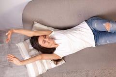 Härlig lycklig ung kvinna som ligger på en soffa royaltyfri fotografi
