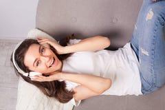 Härlig lycklig ung kvinna som ligger på en soffa och tycker om musik royaltyfri bild
