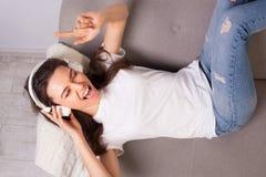 Härlig lycklig ung kvinna som ligger på en soffa och tycker om musik arkivfoto