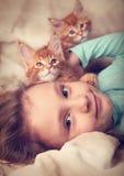 Härlig lycklig ungeflicka som ligger med gulliga två maine tvättbjörnkattungar fotografering för bildbyråer