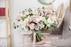 Härlig lyxig bukett av blandade blommor i kvinnahand arbetet av blomsterhandlaren på en blomsterhandel bröllop Royaltyfria Foton