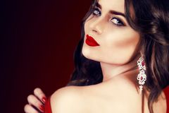Härlig lyxig kvinna med smycken, örhängen Skönhet och tillbehör Sexig brunettflicka med stora röda kanter i en röd klänning arkivfoto