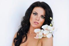 Härlig mörk haired flicka med orkidér på vit Arkivbilder