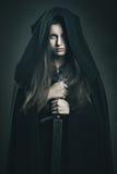 Härlig mörk kvinna med den svarta ämbetsdräkten och svärdet Royaltyfria Bilder