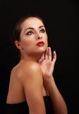 Härlig makeupkvinna som ser upp på svart Fotografering för Bildbyråer