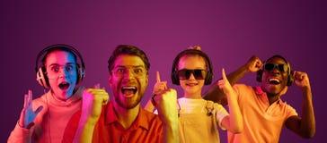 Härlig man och kvinnliga modeller i neonljus som isoleras på purpurfärgad studiobakgrund arkivfoton