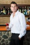 Härlig man som har en martini Arkivbild